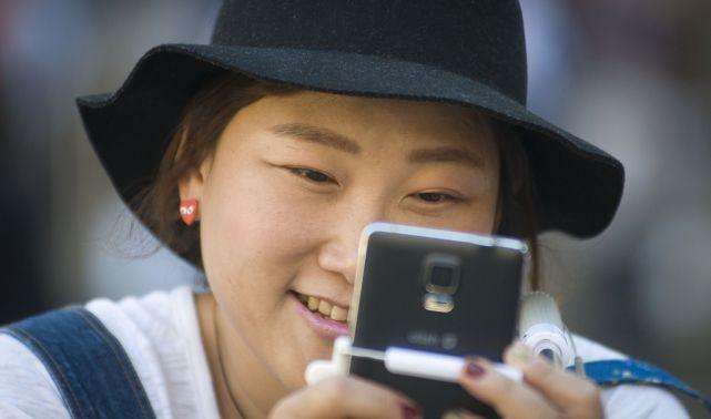 Una turista asiática mira su teléfono móvil. / Juan Barbosa
